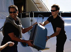 Men loading suit cases onto a yacht