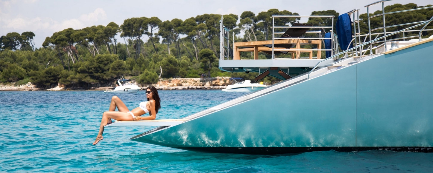 Luxury catamaran Hutine's deck with woman sunbathing