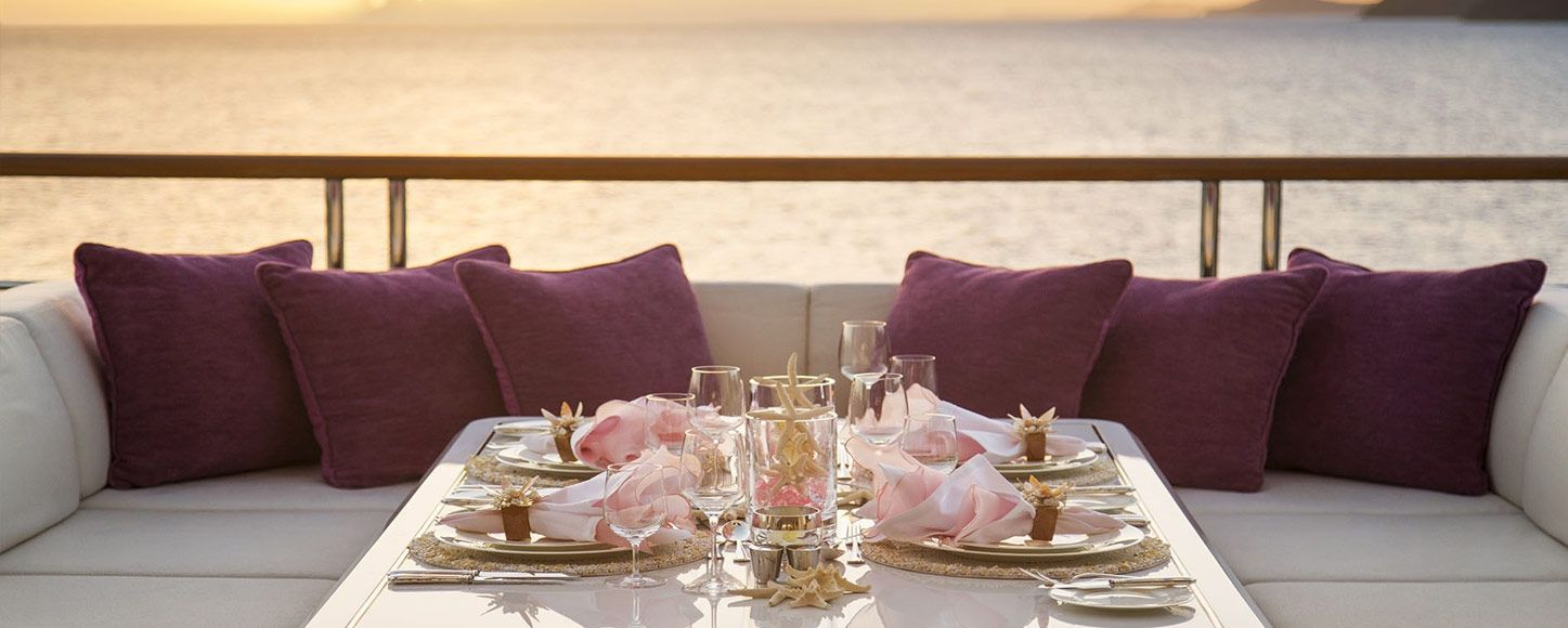Charter yacht Solandge table on deck at sunset