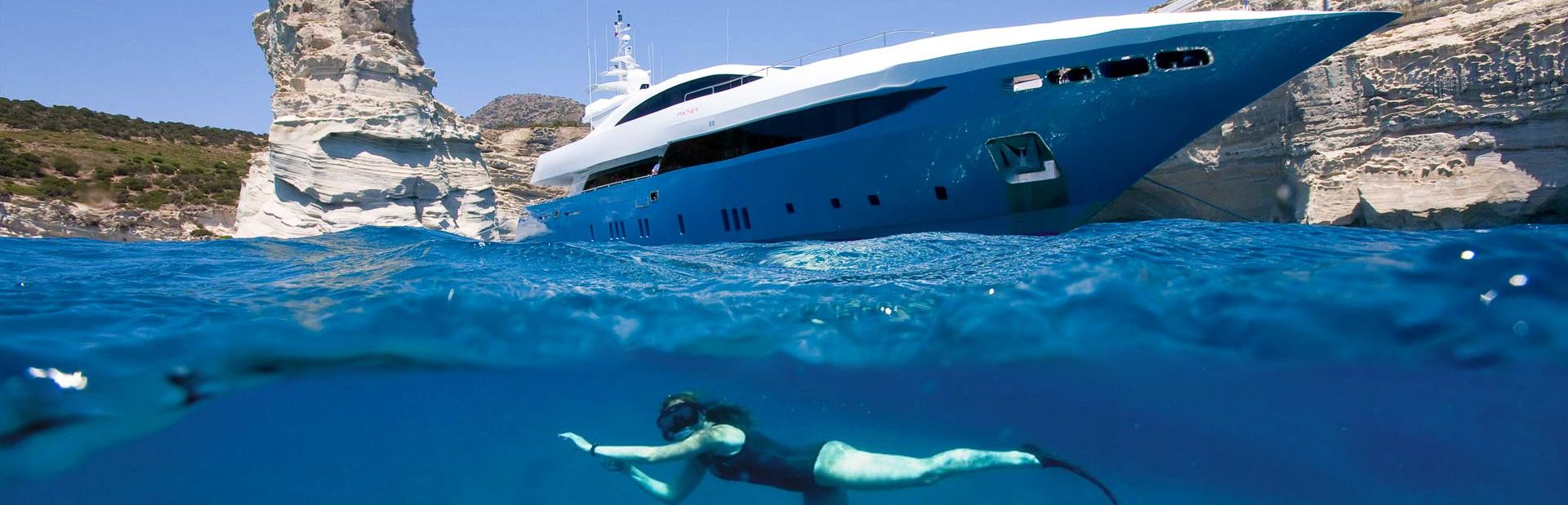 person underwater snorkeling and superyacht
